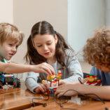 3 kids playing building blocks